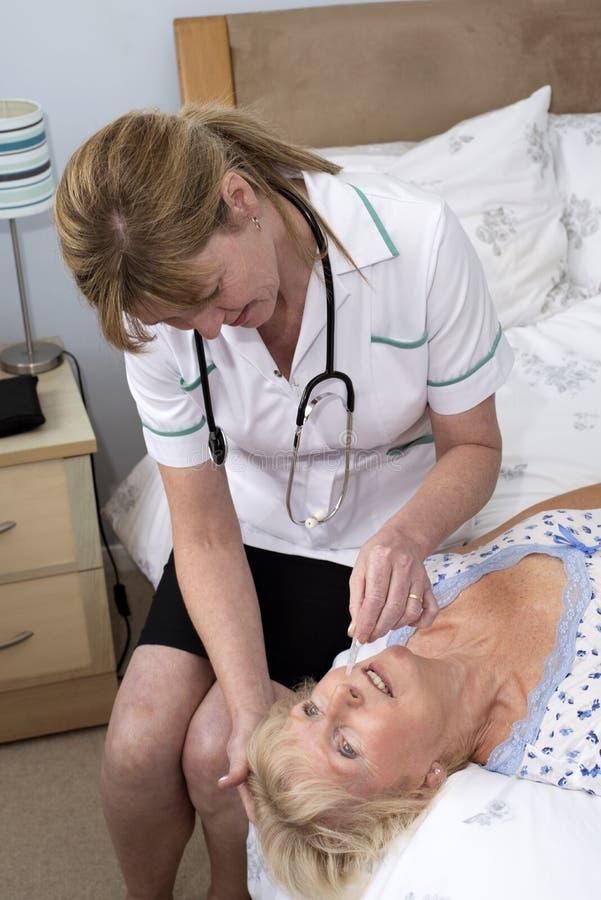 Infirmière donnant des baisses de nez au patient images libres de droits
