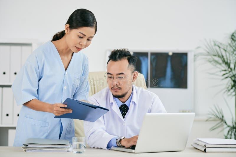 Infirmière donnant le document au docteur photos libres de droits