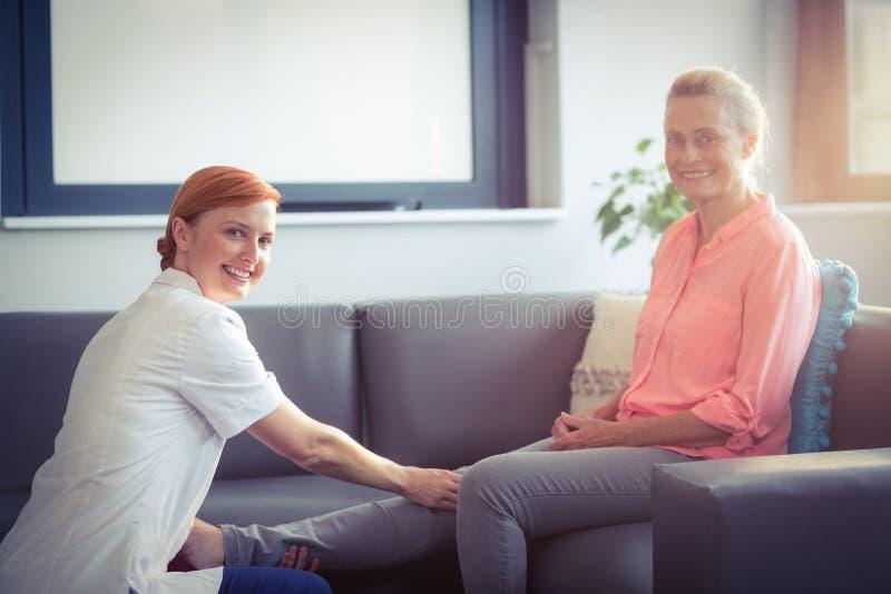 Infirmière donnant le massage de jambe à la femme images libres de droits