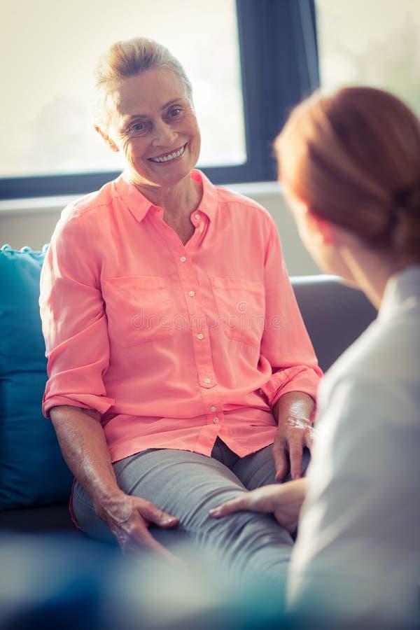 Infirmière donnant le massage de jambe à la femme images stock