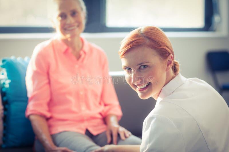 Infirmière donnant le massage de jambe à la femme photos libres de droits