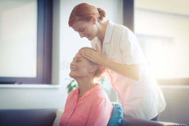 Infirmière donnant le massage principal à la femme photographie stock