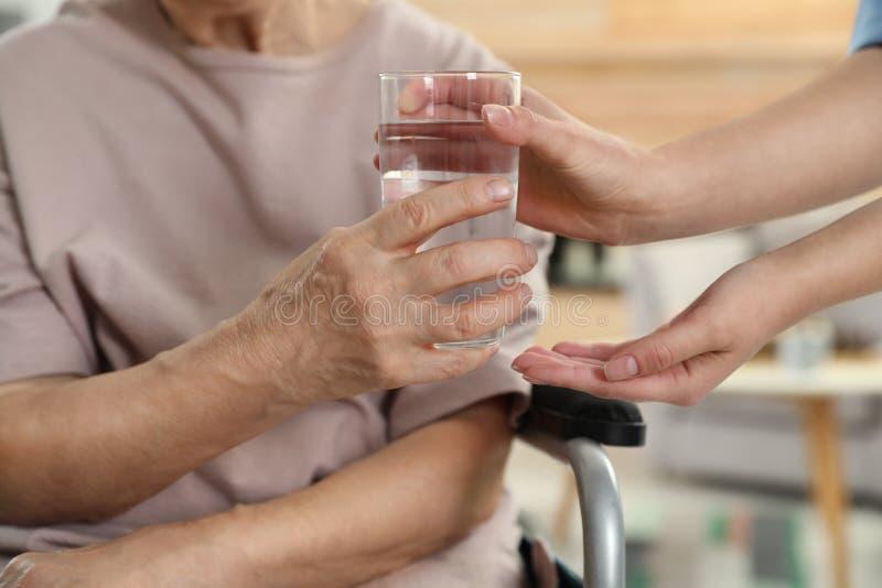 Infirmière donnant le verre de l'eau à la femme agée à l'intérieur, plan rapproché photo libre de droits