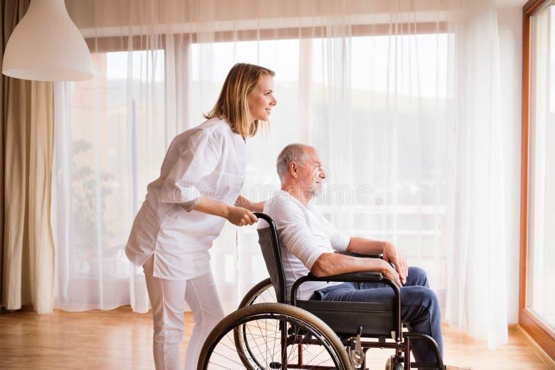 Infirmière et homme supérieur dans le fauteuil roulant pendant la visite à la maison images libres de droits