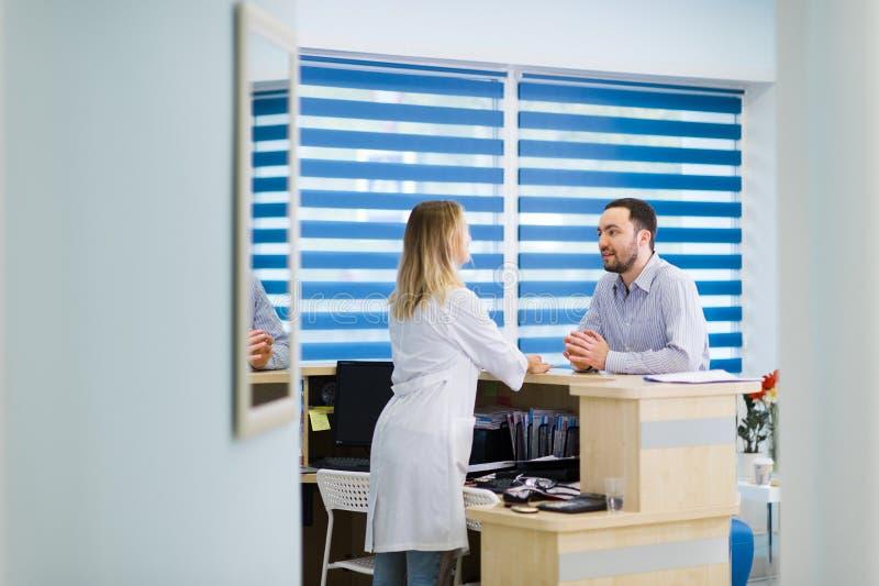 Infirmière et patient conversant à la réception dans l'hôpital images libres de droits