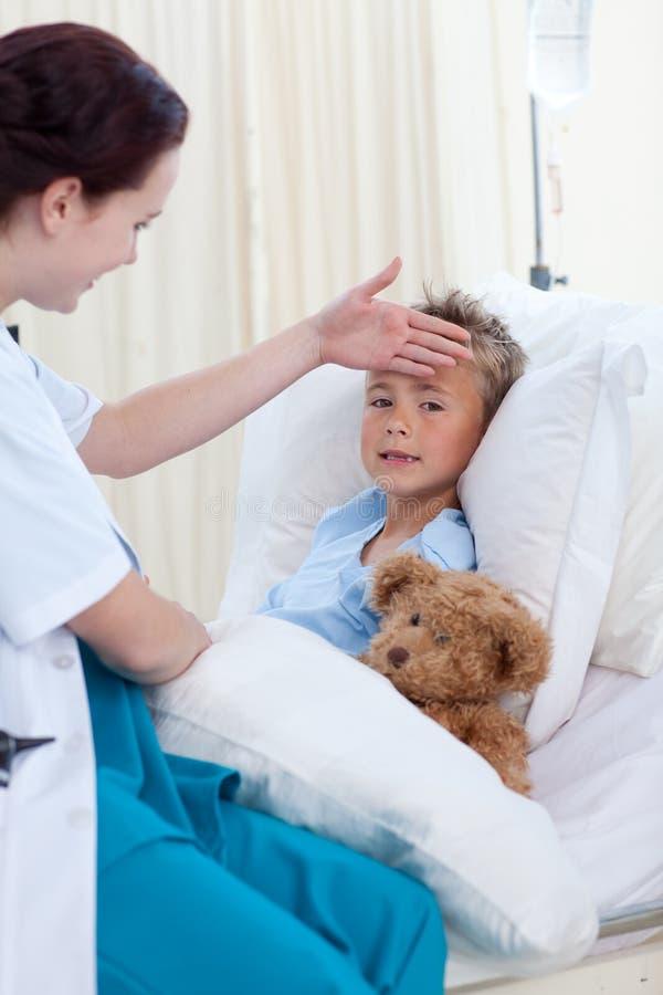 Infirmière examinant la fièvre d'un garçon image libre de droits