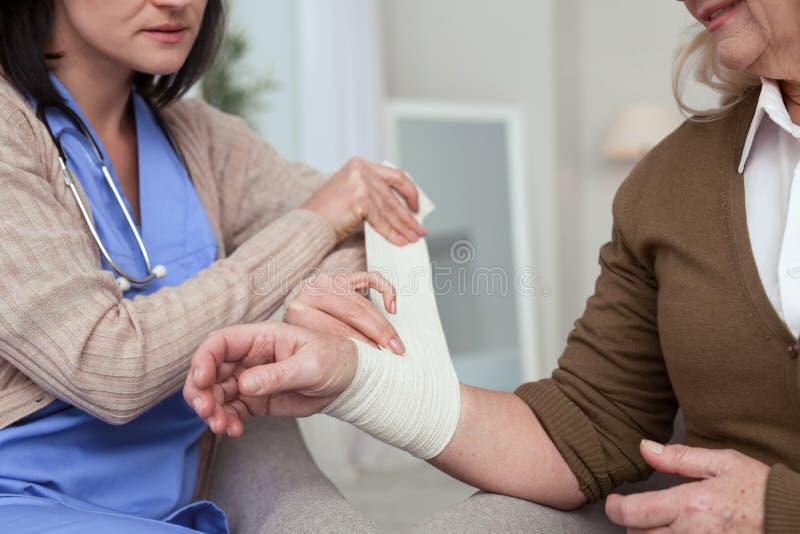 Infirmière expérimentée enveloppant la main de femme plus âgée images stock