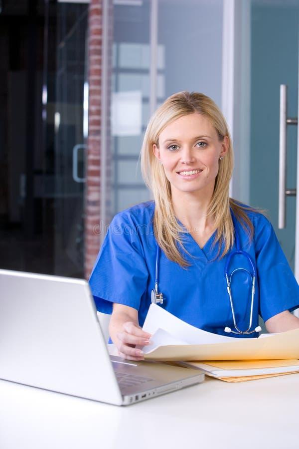 Infirmière féminine à un fonctionnement de bureau photo stock