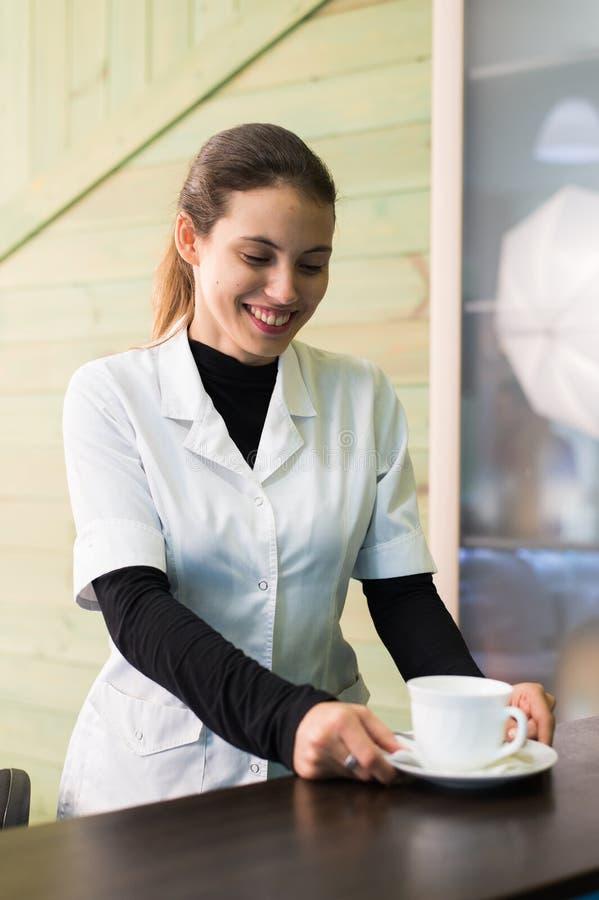 Infirmière féminine au bureau faisant le café fonctionnant dans un bureau moderne photos stock