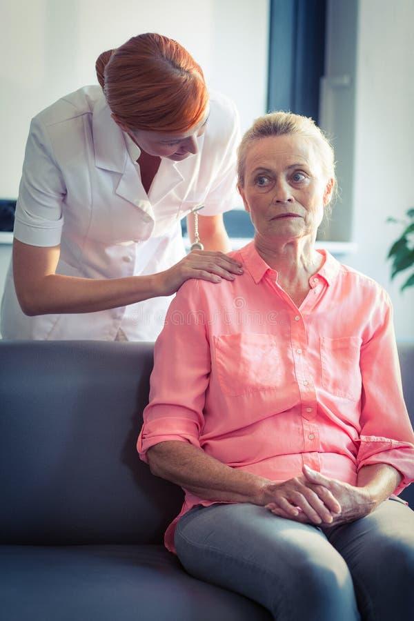 Infirmière féminine consolant la femme supérieure photographie stock libre de droits