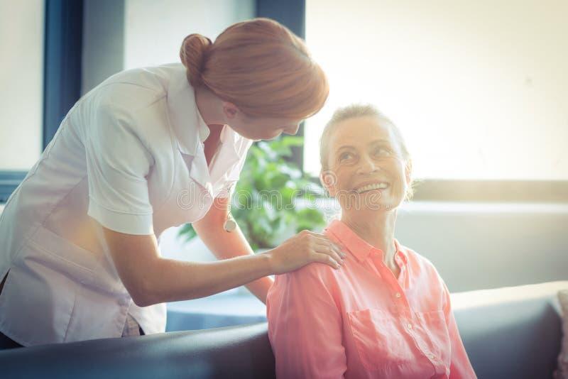 Infirmière féminine consolant la femme supérieure images libres de droits
