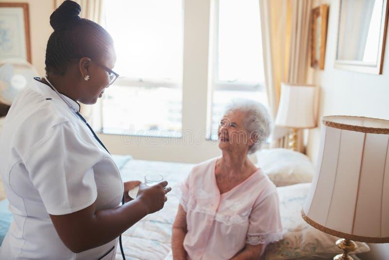 Infirmière féminine donnant la médecine au patient supérieur à la maison photos libres de droits