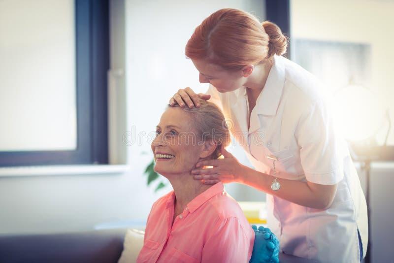 Infirmière féminine donnant le massage principal à la femme photo stock