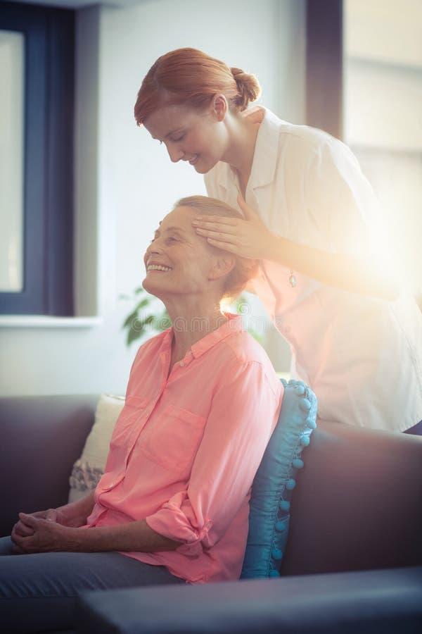 Infirmière féminine donnant le massage principal à la femme photographie stock