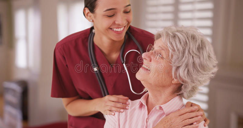 Infirmière féminine hispanique regardant et souriant avec le Caucasien supérieur photographie stock