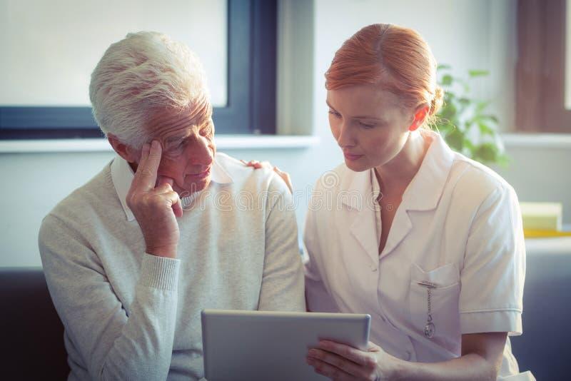 Infirmière féminine montrant le rapport médical à l'homme supérieur sur le comprimé numérique photos stock