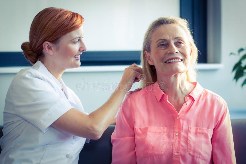 Infirmière féminine peignant des cheveux de femme supérieure photographie stock