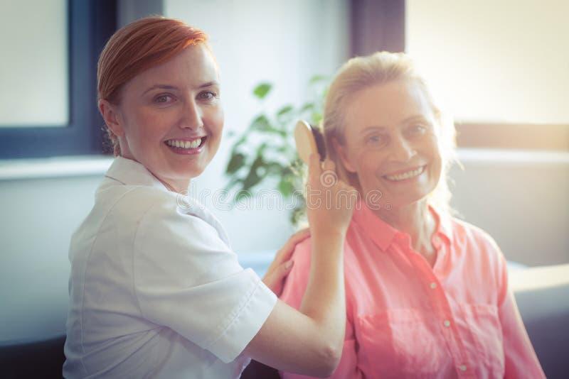 Infirmière féminine peignant des cheveux de femme supérieure image libre de droits