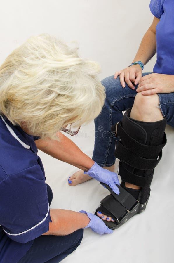 Infirmière Fitting une botte orthopédique à Madame avec une jambe cassée photo stock