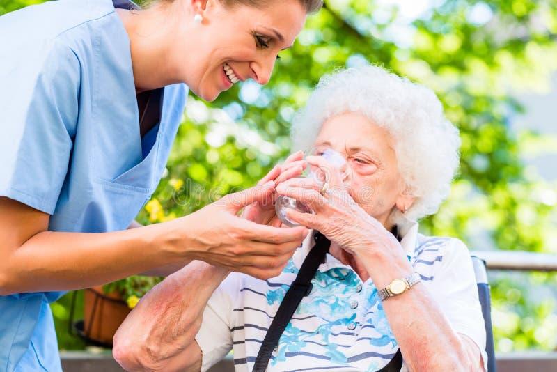 Infirmière gériatrique donnant le verre de l'eau à la femme supérieure photos stock
