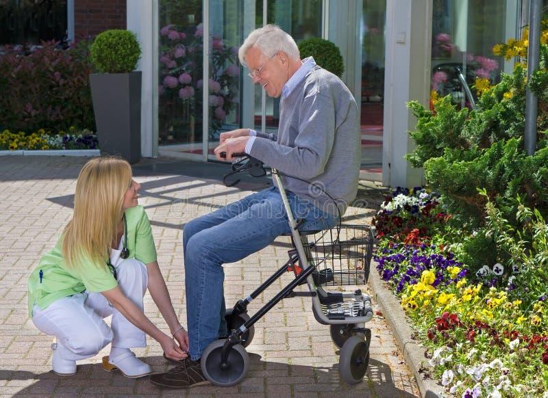 Infirmière Helping Senior Man avec le marcheur pour attacher des chaussures image stock