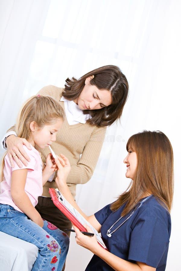 Infirmière : Infirmière Takes Temperature de petite fille photo stock