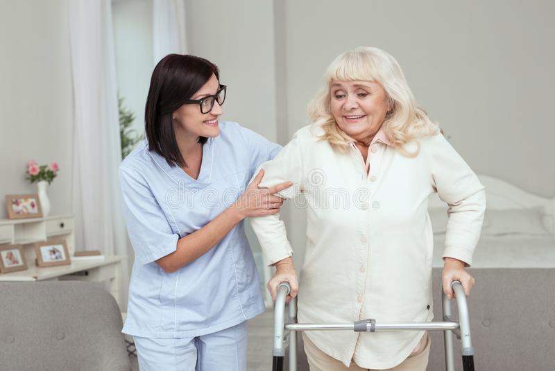 Infirmière joyeuse assurant l'appui à une femme plus âgée photo stock