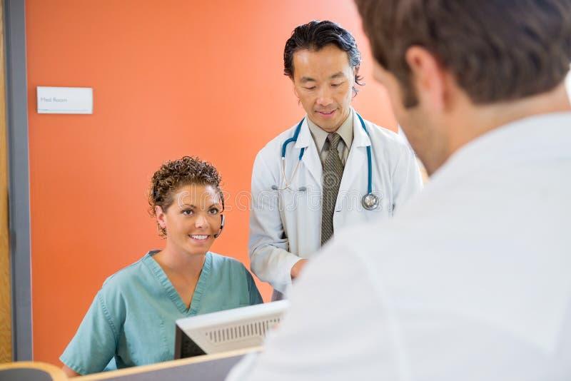 Infirmière Looking At Patient avec docteur Standing By image libre de droits