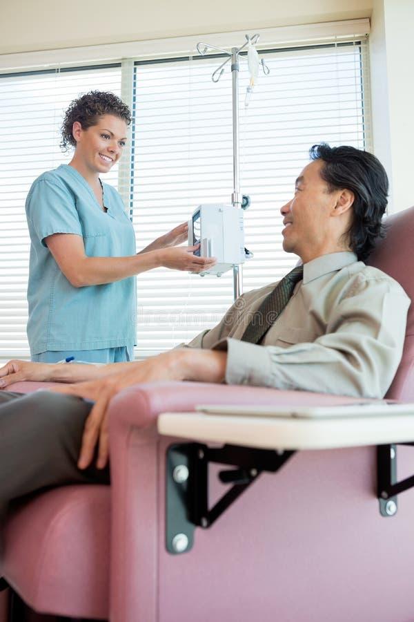 Infirmière Looking At Patient tout en actionnant IV images libres de droits
