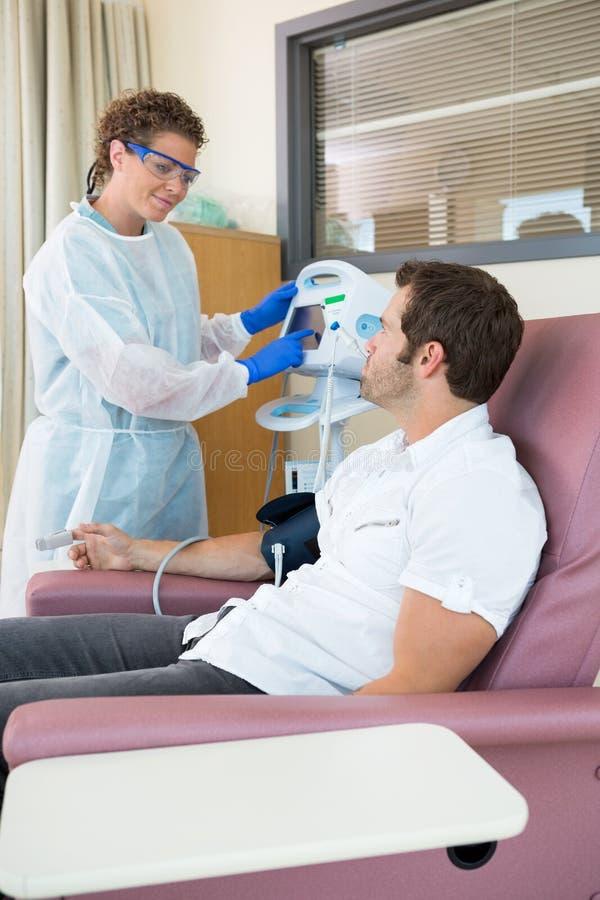 Infirmière Looking At Patient tout en actionnant le battement de coeur image libre de droits