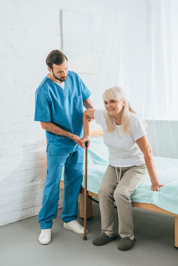 infirmière masculine aidant la femme supérieure photographie stock