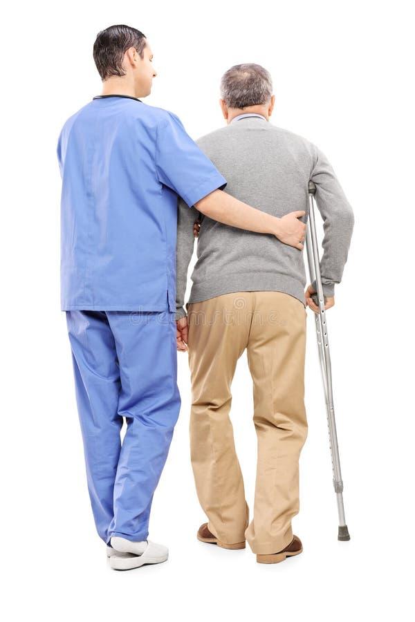 Infirmière masculine aidant un monsieur plus âgé photographie stock libre de droits