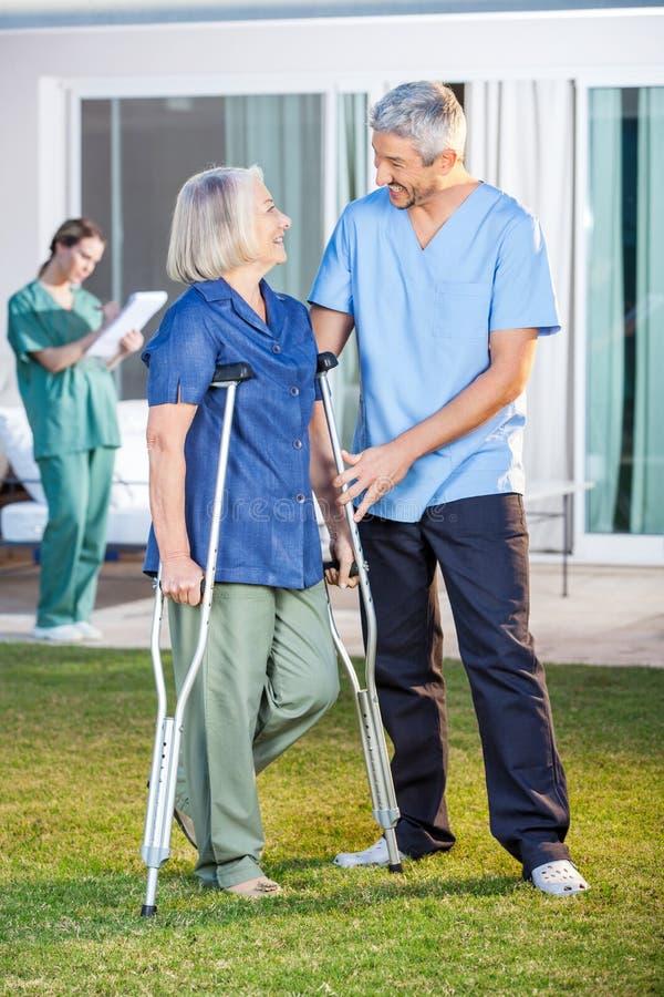 Infirmière masculine Assisting Senior Woman pour utiliser des béquilles photographie stock