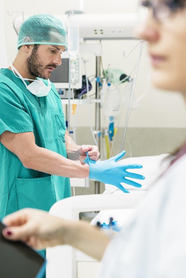 Infirmière masculine mettant des gants dans l'hôpital photo stock