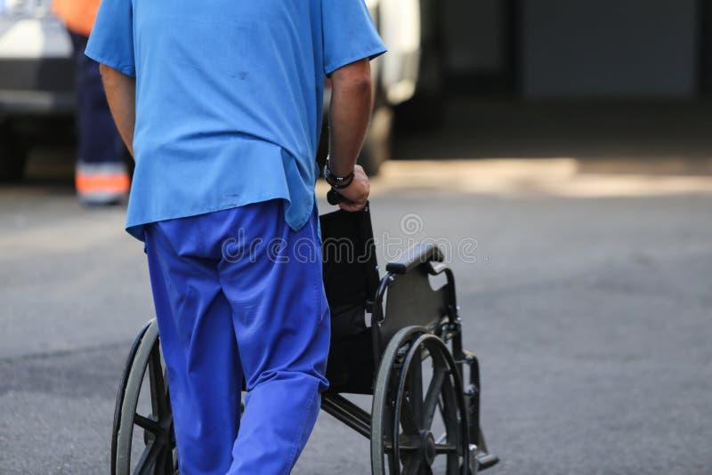 Infirmière masculine poussant un fauteuil roulant vide image libre de droits
