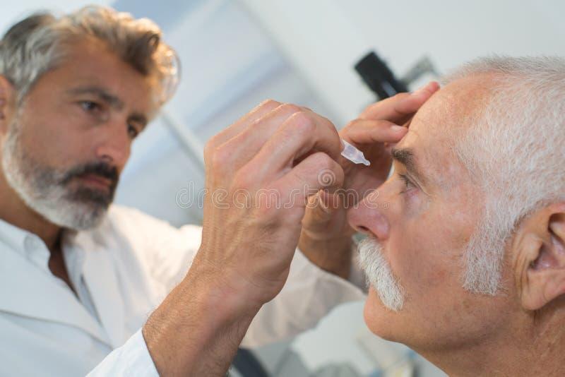 Infirmière mettant des gouttes pour les yeux aux yeux de patients image stock