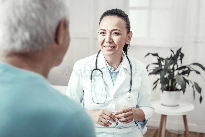 Infirmière mignonne qualifiée souriant et ayant la consultation images stock