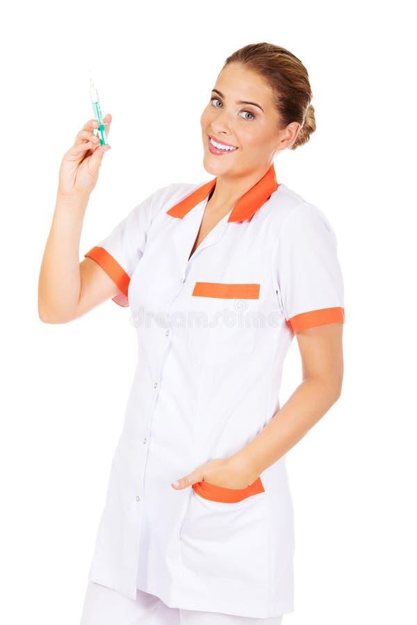 Infirmière ou docteur féminine de sourire avec une seringue à disposition image stock