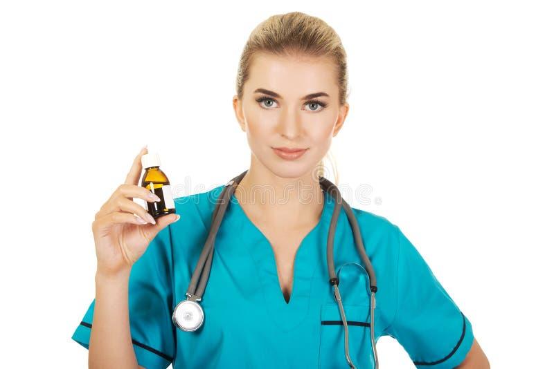 Infirmière ou docteur féminine tenant la bouteille de médecine dans la main photo stock