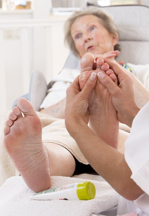 Infirmière ou donateur de soin traitant le pied d'une femme supérieure images libres de droits