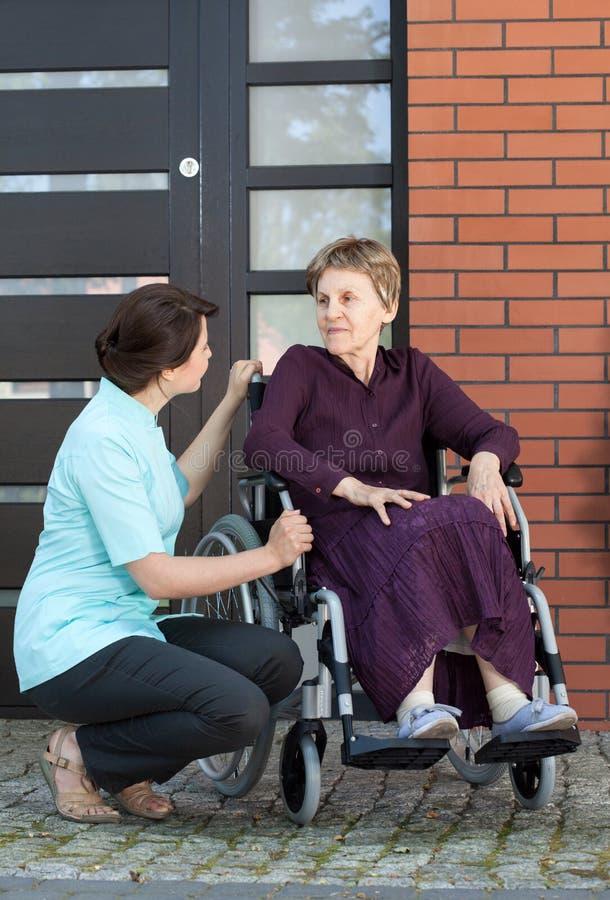 Infirmière parlant avec la femme supérieure sur le fauteuil roulant image libre de droits