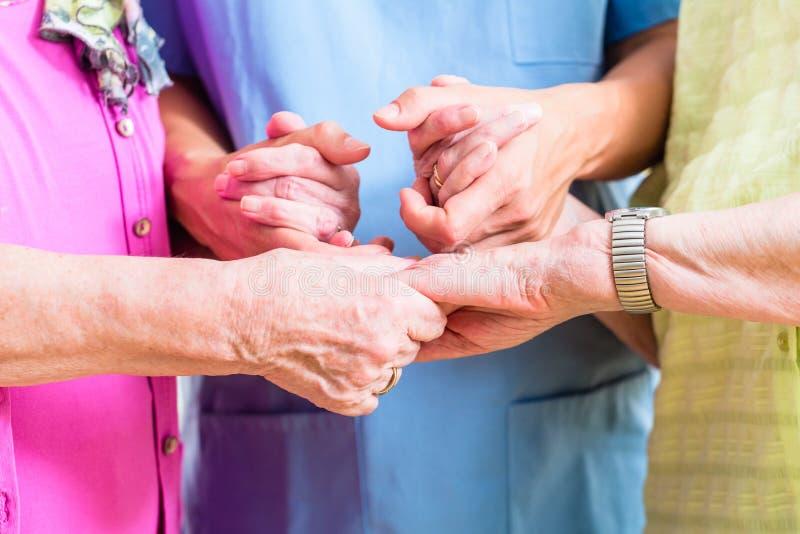 Infirmière pluse âgé de soin avec deux femmes supérieures image stock