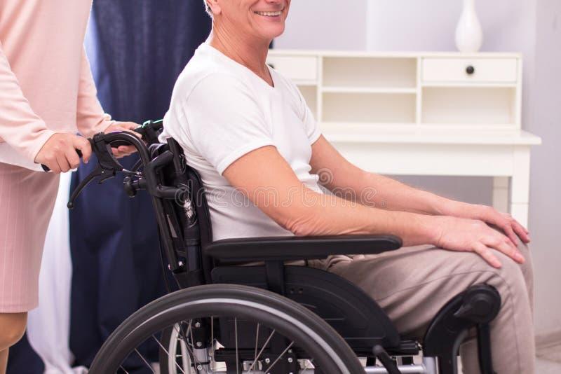 Infirmière poussant le fauteuil roulant avec l'homme dans lui photographie stock