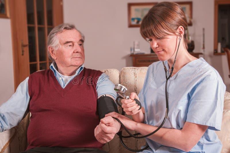 Infirmière prenant la tension artérielle à la maison photo libre de droits