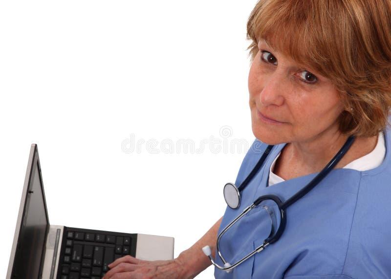 Infirmière recherchant tandis que sur l'ordinateur portatif photo stock