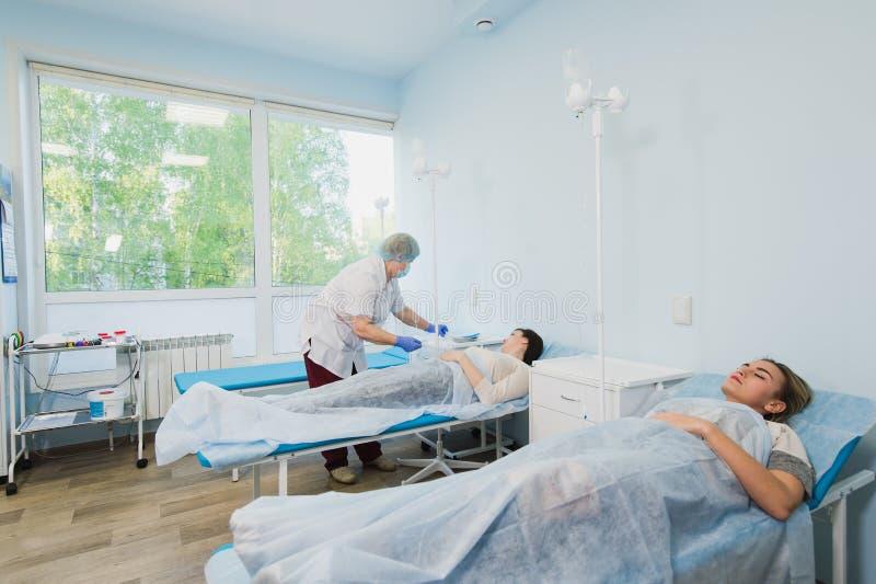 Infirmière reliant un égouttement intraveineux dans la chambre d'hôpital images libres de droits