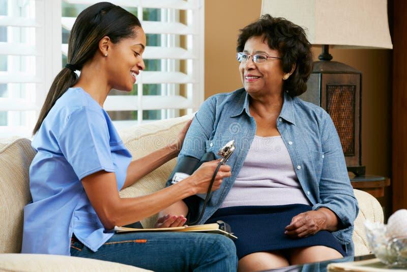 Infirmière rendant visite au patient féminin supérieur à la maison photographie stock libre de droits