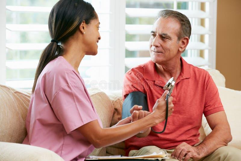 Infirmière rendant visite au patient mâle supérieur à la maison images libres de droits