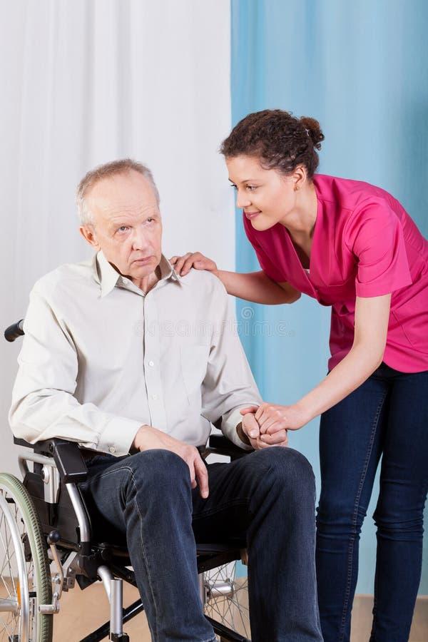 Infirmière s'inquiétant de l'homme handicapé photo stock