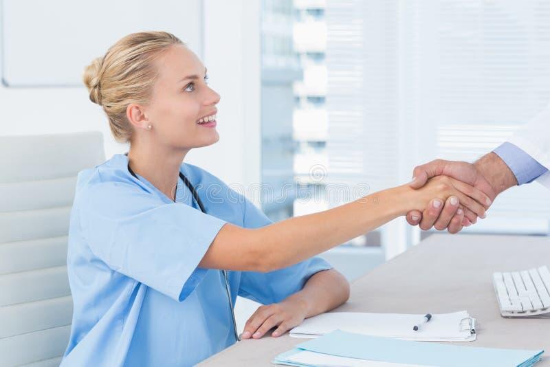 Infirmière serrant la main de son collègue photographie stock libre de droits